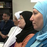 Usama Alshaibi sits in a row with Arab women wearing their hijab