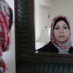 Amal Abusumayah wearing her hijab looks in the mirror