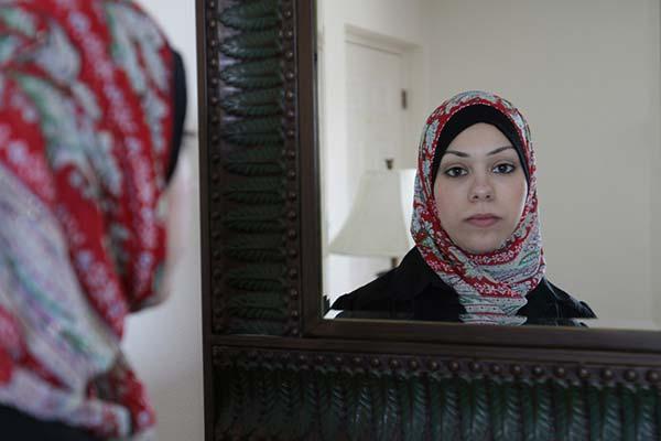 Amal Abusumayah wearing her hijab looks in the mirror