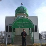 An imam stands in front of his mosque with a green awning