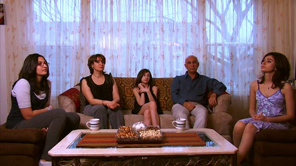 The Jassar Family sit in the living room of their Chicago apartment