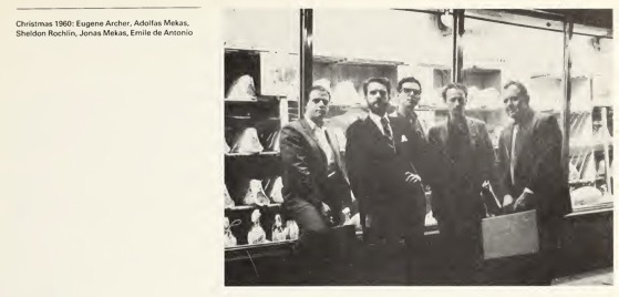 Men wearing suits posing in front of a storefront window